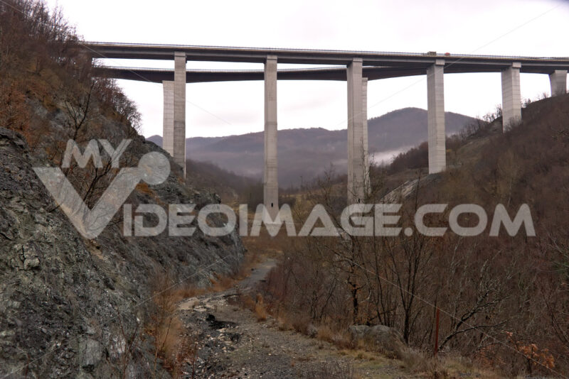 Highway of the Cisa. Asphalt strip running through the mountains of Tuscany and Emilia. Bridge with high pillars in reinforced concrete. - MyVideoimage.com