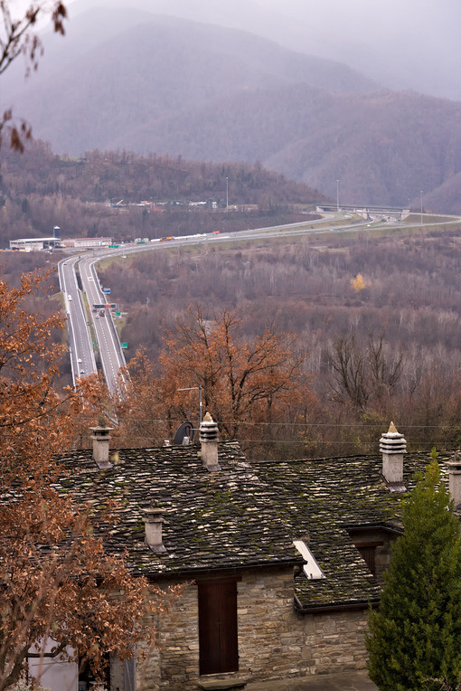 Highway of the Cisa. Asphalt strip running through the mountains of Tuscany and Emilia. Stone house and trees with yellow leaves. - MyVideoimage.com