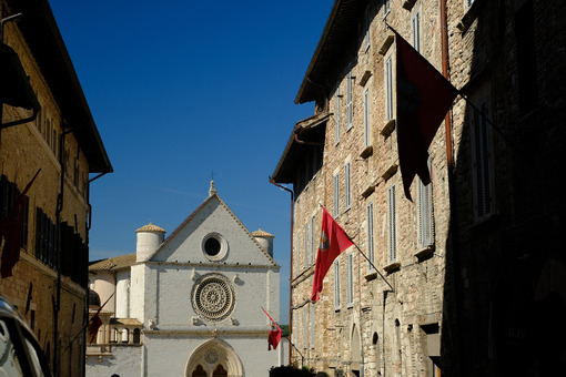 Historic Via San Francesco in Assisi leading to the famous basilica. Flags fly on the facades of the stone and brick houses. - LEphotoart.com