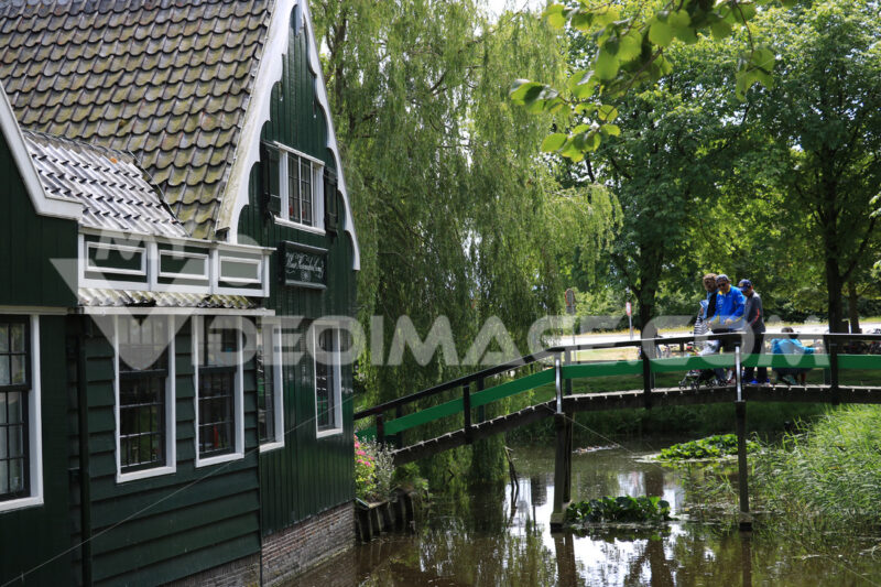 House on the stream. Wooden house on the stream. River bridge with people and childre - MyVideoimage.com | Foto stock & Video footage