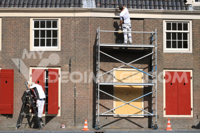 House painter paints a house. Facade with brick wall and white w - MyVideoimage.com