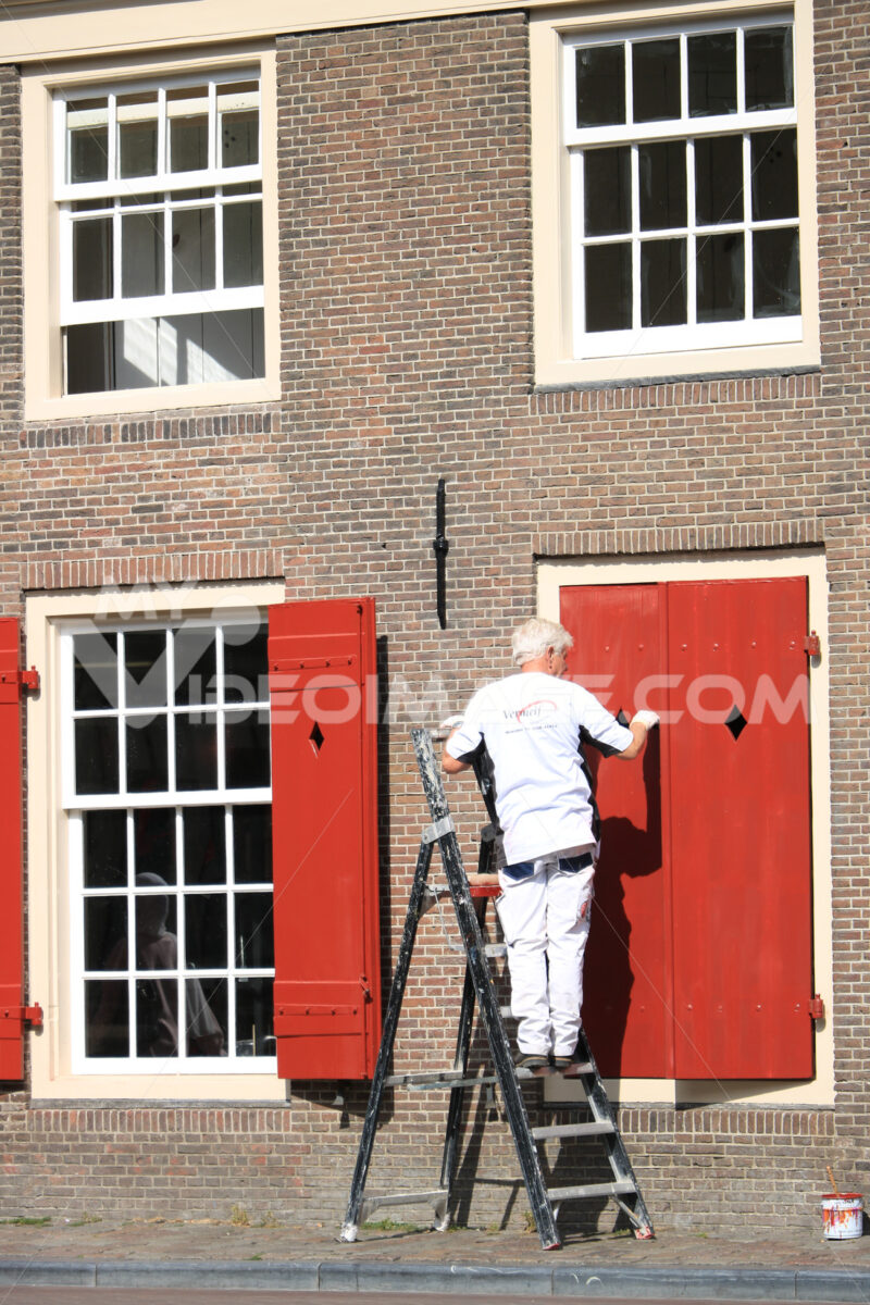 House painter paints a red shutter. Facade of a house with a bri - MyVideoimage.com