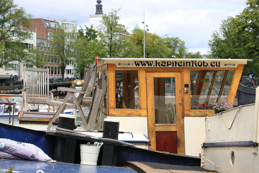 Houseboats and boats in an Amsterdam canal. Boats converted into dwellings anchored on the city canals. - MyVideoimage.com