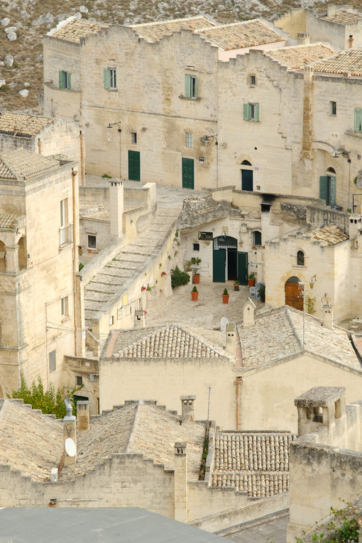 Houses, roads and alleys in the Sassi of Matera. Typical dwellings carved into the rock and with facades of beige tuff blocks. - MyVideoimage.com
