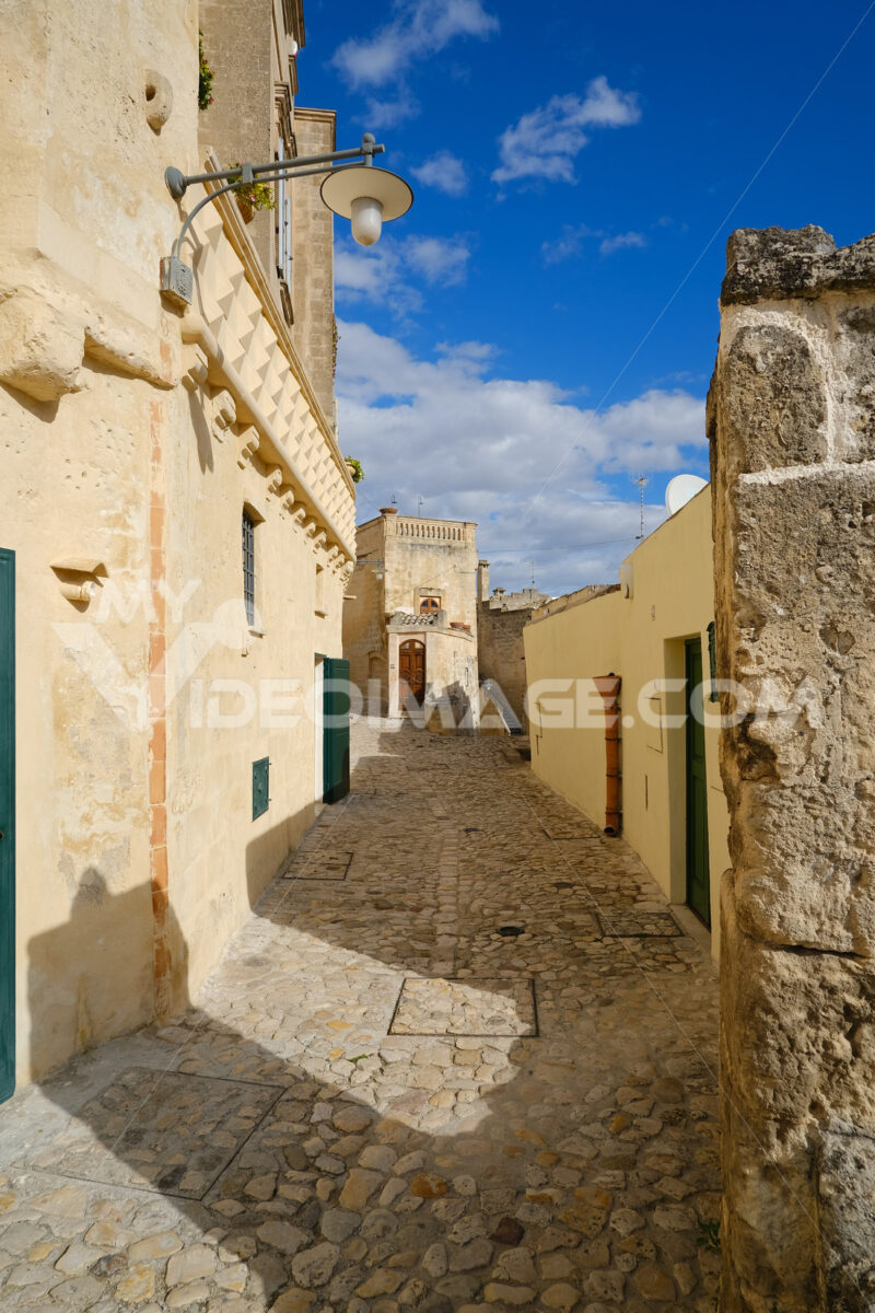 Houses, roads and alleys in the Sassi of Matera. Typical dwellings carved into the rock and with facades of beige tuff blocks. - LEphotoart.com