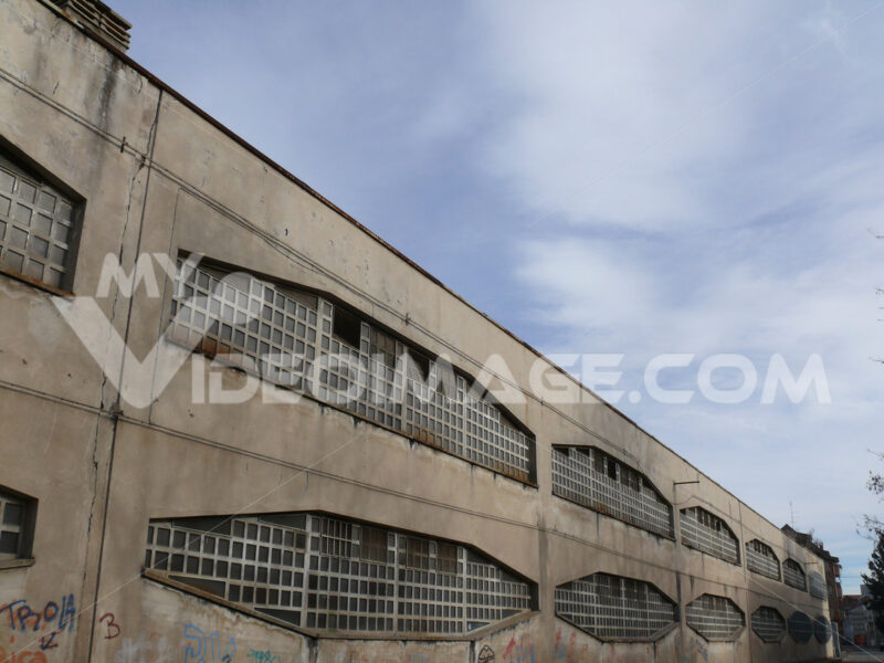 Industrial archeology buildings in the city of Busto Arsizio. Facade of an old factory with glass block windows. - MyVideoimage.com