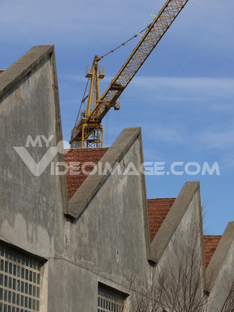 Industrial archeology buildings in the city of Busto Arsizio. Facade of ancient factory shed. Construction crane. Foto Busto Arsizio photo