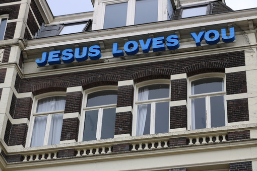 "It teaches ""Jesus loves you"" on the facade of a building. - MyVideoimage.com"