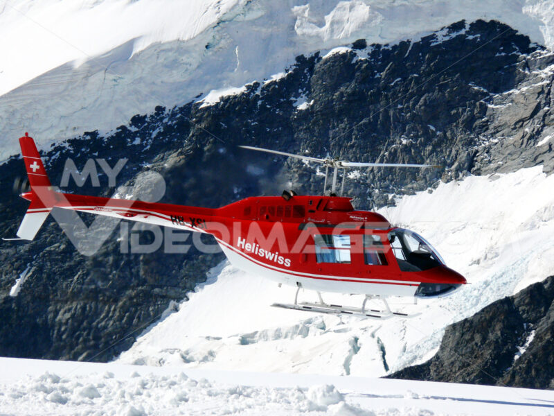 Jungfrau, Switzerlan, 08/06/2009. Red helicopter on high mountai - MyVideoimage.com