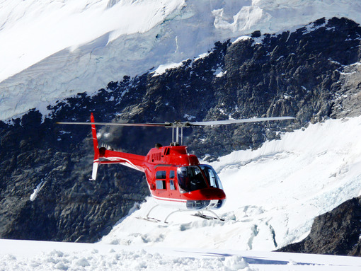 Jungfrau, Switzerlan. Red helicopter on high mountain snow - MyVideoimage.com