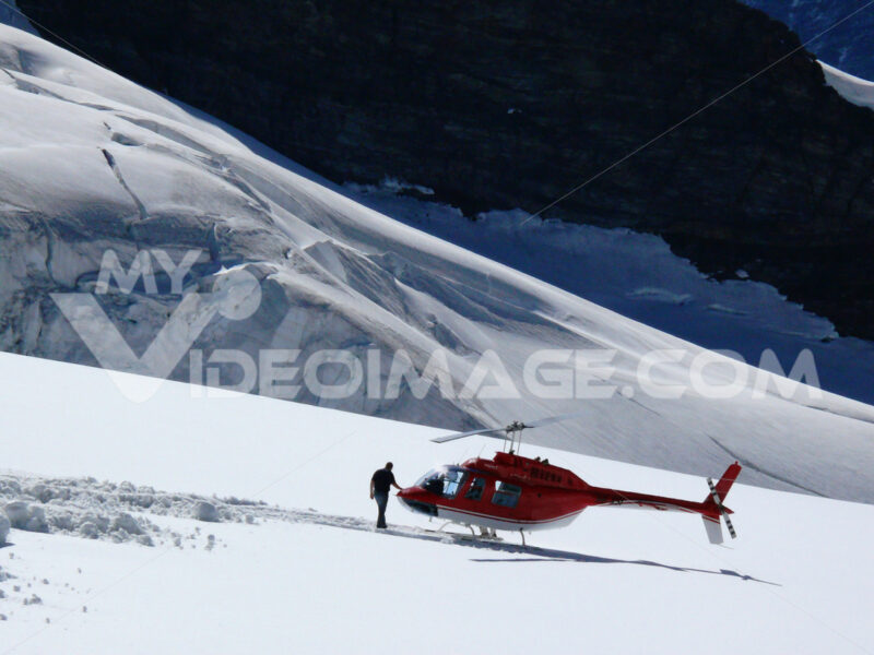 Jungfrau, Switzerland. 08/06/2009. Red colored helicopter and ma - MyVideoimage.com