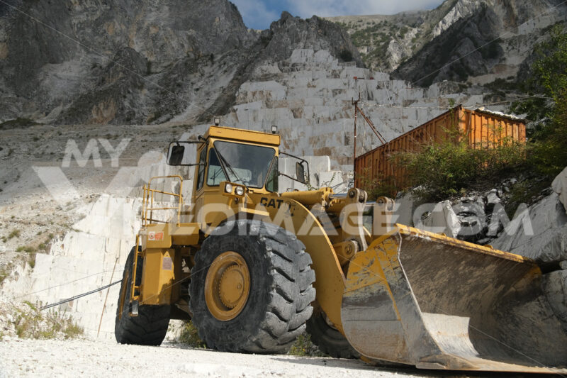 Large mechanical shovel in a quarry of white Carrara marble. Blocks of white marble deposited in the square. - LEphotoart.com