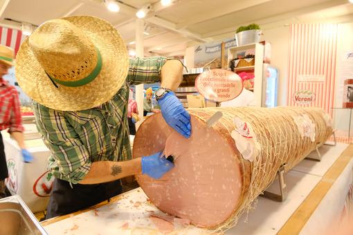 Large mortadella salami from Bologna. A pork butcher with a cowboy hat cuts a big salami. - MyVideoimage.com