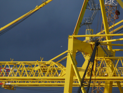 Large yellow crane in a shipyard. Cloudy sky background. - MyVideoimage.com