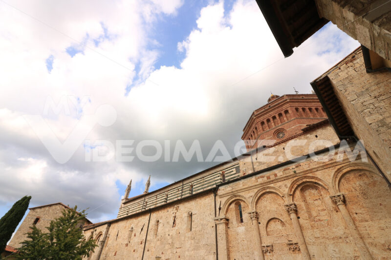 Lateral facade of the cathedral of Massa Marittima in the Tuscan Maremma. Blue sky with clouds. - MyVideoimage.com