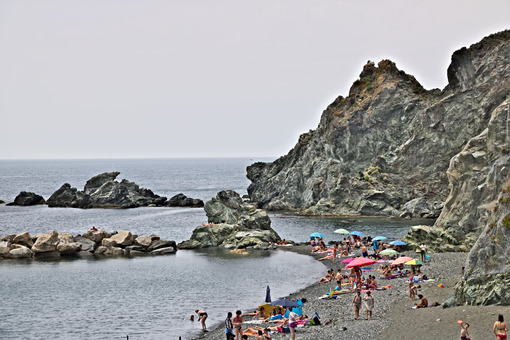 Levanto, near Cinque Terre. 06/09/2019. Some people tan in the sun. In the background the cliff. The Cinque Terre sea is ideal for sports activities. - LEphotoart.com