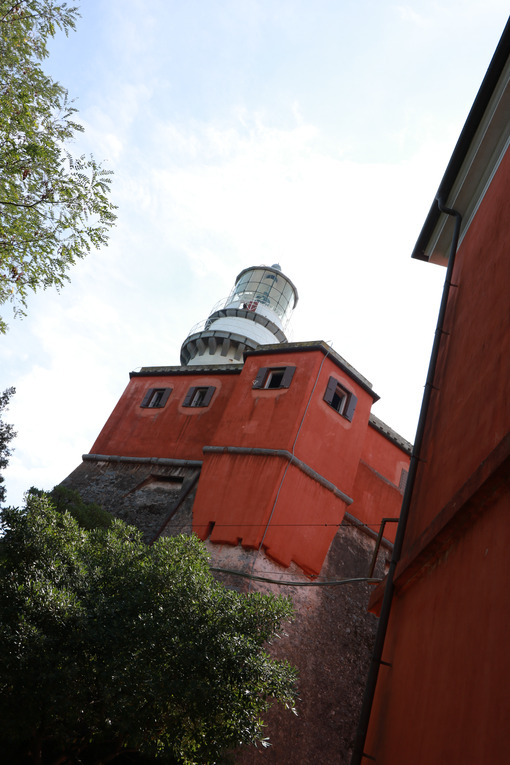 Lighthouse of the Isola del Tino, in the Gulf of La Spezia,  Near Cinque Terre. Red painted building and white tower with glass. - LEphotoart.com