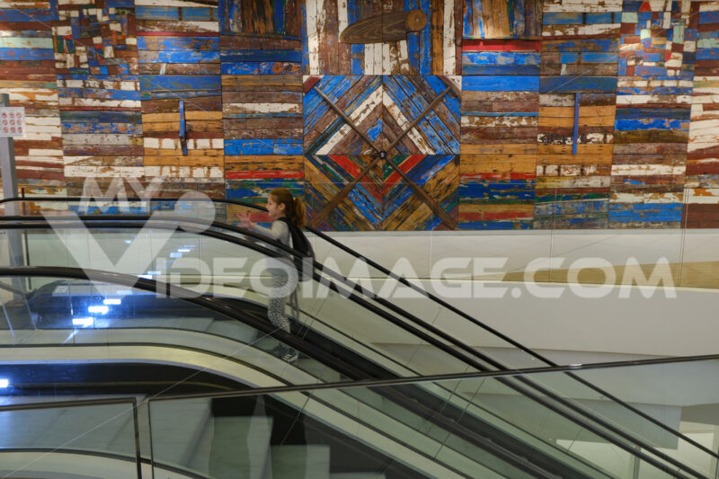 Little girl on an escalator at Bari airport. Decorative panel with wooden slats made from old boats. - MyVideoimage.com