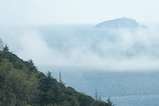 Low clouds over the Mediterranean sea with fog. Background with Tino island and hill with vegetation and trees. - MyVideoimage.com