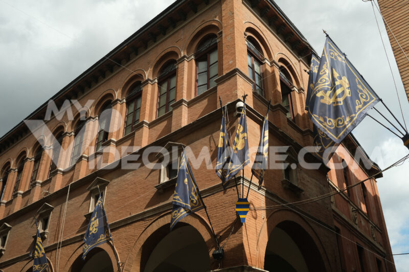 Main street of Foligno with waving flags on the facades of the houses. The ancient palaces lit by the sun with cloudy sky. - MyVideoimage.com