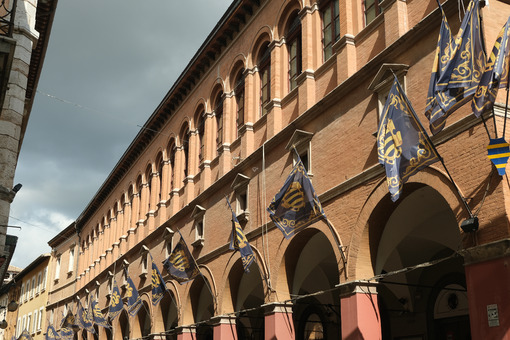 Main street of Foligno with waving flags on the facades of the houses. The ancient palaces lit by the sun with cloudy sky. - LEphotoart.com
