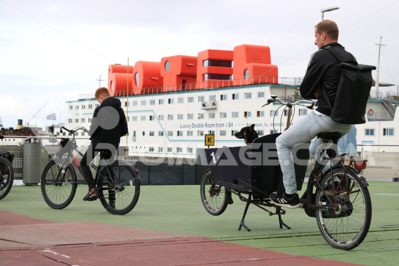 Man and black dog on a bicycle await the ferry. In the backgroun - MyVideoimage.com