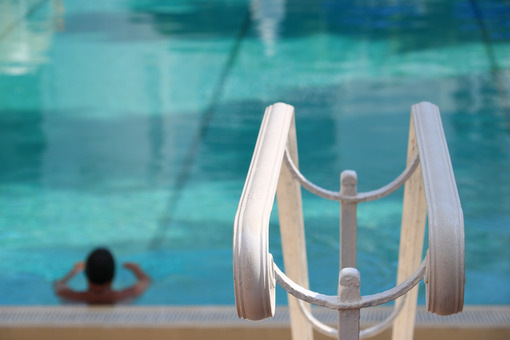 Man in the pool with green water. In the foreground, a white handrail. - MyVideoimage.com