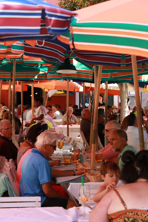 Many people sitting at tables, under colored umbrellas, in a restaurant in the village of Vernazza in the Cinque Terre. - MyVideoimage.com
