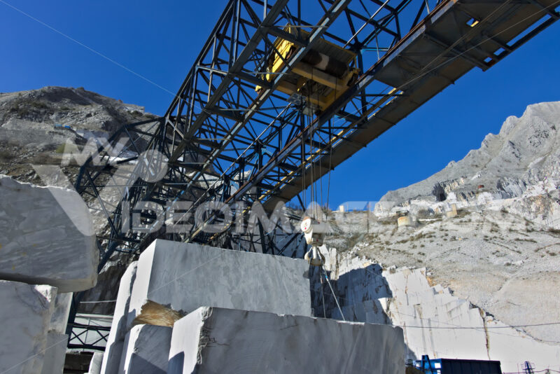 Marble deposit with overhead crane. Apuan Alps, Carrara, Tuscany, Italy. March 28, 2019. An overhead crane in a white marble quarry. Cave marmo. - MyVideoimage.com | Foto stock & Video footage