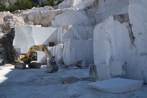 Marble wall with excavator in a quarry. Crawler excavator in a marble quarry near Carrara. Stock photos. - MyVideoimage.com | Foto stock & Video footage