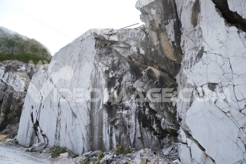 Marble wall. Carrara white marble wall. Rough natural marble surface in a quarry. Stock photos. - MyVideoimage.com | Foto stock & Video footage
