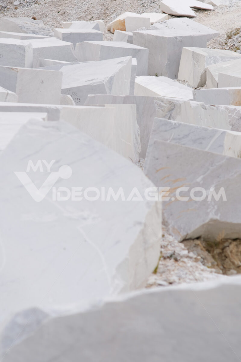 Marmo bianco di Carrara. Blocks of white Carrara marble deposited in a square near the quarries. Foto stock royalty free. - MyVideoimage.com | Foto stock & Video footage