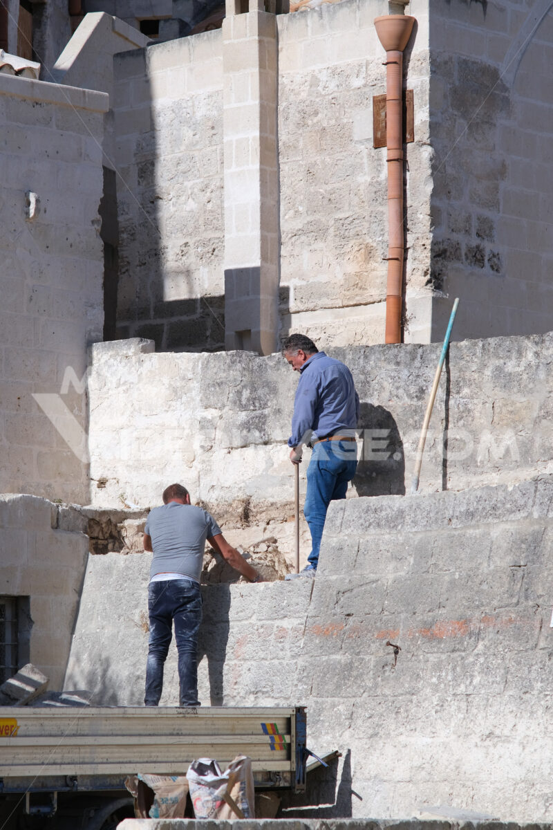 Masons at work in the construction of a wall with stone blocks in Matera. - MyVideoimage.com
