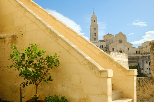 Matera alley with lemon plant and church. A Mediterranean courtyard with leaves of a small tree blowing in the wind. - LEphotoart.com