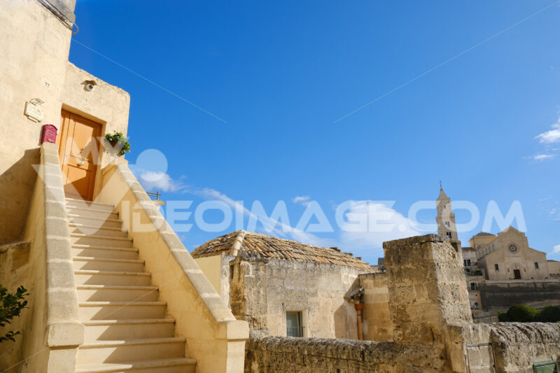 Matera alley with staircase and church. A Mediterranean courtyard with leaves of a small tree blowing in the wind. - MyVideoimage.com