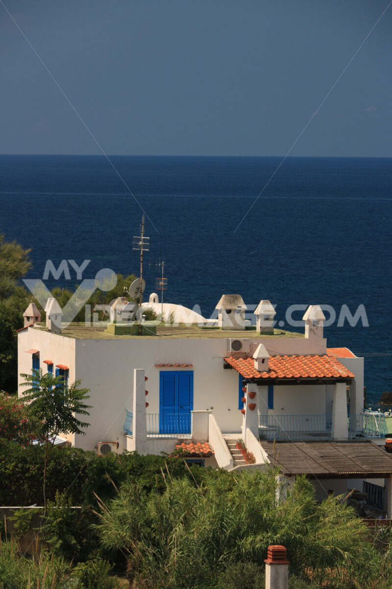 Mediterranean style holiday home with white walls and fireplaces. Sea and blue sky background. - MyVideoimage.com