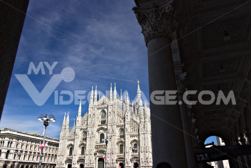Milan Cathedral facade with  blue sky.  In the foreground the arches of the portico. - MyVideoimage.com