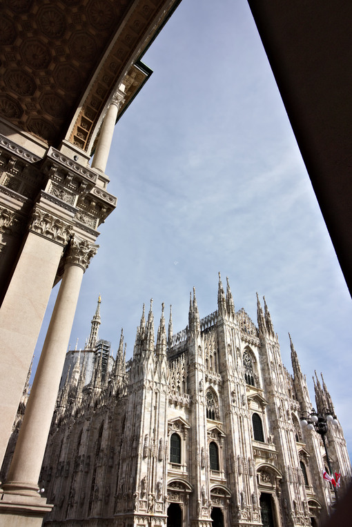 Milan Cathedral facade with blue sky. In the foreground the arches of the portico. Città italiane.