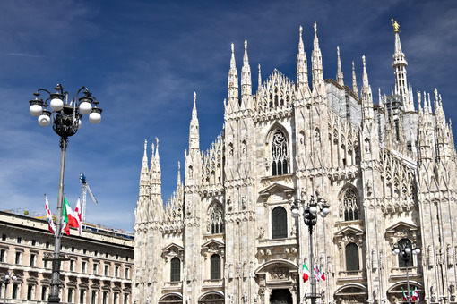 Milan Cathedral facade with flags on blue sky. Flags waving on the blue sky. Città italiane.