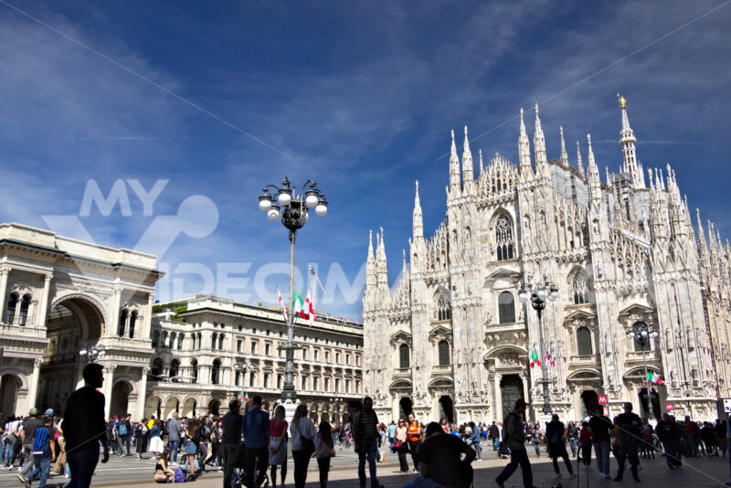 Milan Cathedral facade with flags on blue sky. The facade of the cathedral with many people walking. Flags waving on the blue sky. - MyVideoimage.com