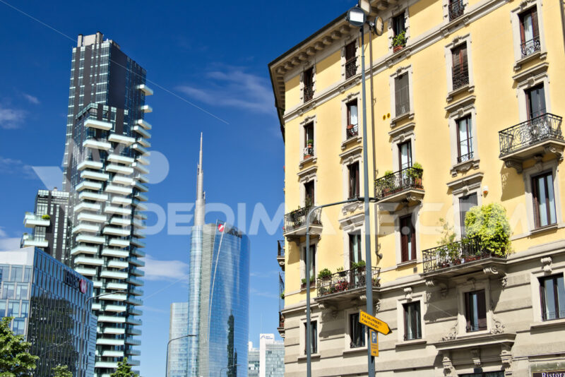 Modern buildings, skyscrapers, roads and traffic in Milano. Tower buildings, glass skyscrapers. Diamond Tower and car traffic on Via della Conciliazione. - MyVideoimage.com