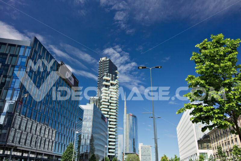 Modern buildings, skyscrapers, roads and traffic in Milano. Tower buildings, glass skyscrapers. Diamond Tower and car traffic on Via della Conciliazione. - MyVideoimage.com