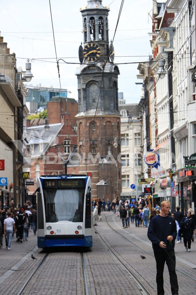 Modern tram in the center of Amsterdam, front view with the tower. Amsterdam foto. Amsterdam photo
