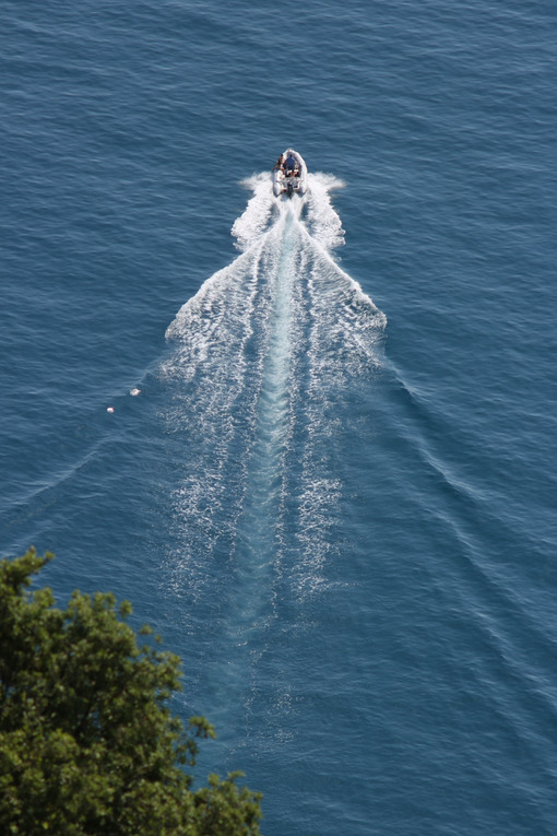 Motorboat takes off in the Ligurian sea at the Cinque Terre. Top view of the path. - MyVideimage.com