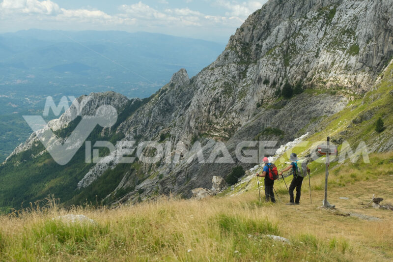 Mountain path on the Alpi Apuane. People on the trail on top of a mountain in the Apuan Alps in Tuscany. Stock photos. - MyVideoimage.com | Foto stock & Video footage