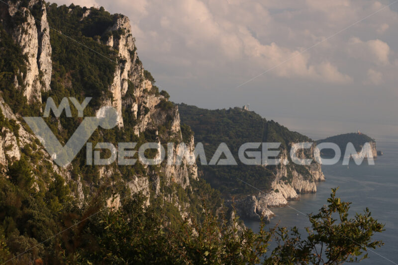 Mountains overlooking the sea near the Cinque Terre. In the background the church of Portovenere and the islands of Palmaria and Tino. Photo at sunset. - MyVideoimage.com
