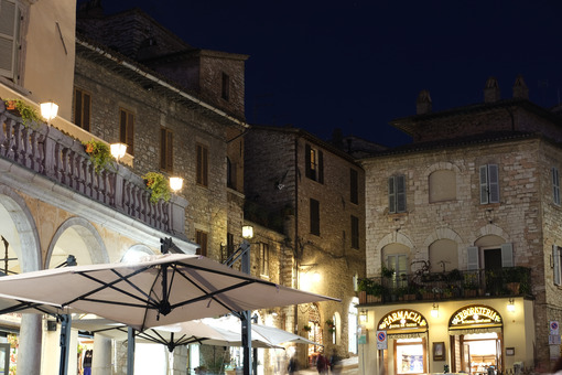 Municipality of Assisi square with old pharmacy and bar area. Illuminated signs in the city of San Francesco with the lights of the night. - MyVideoimage.com