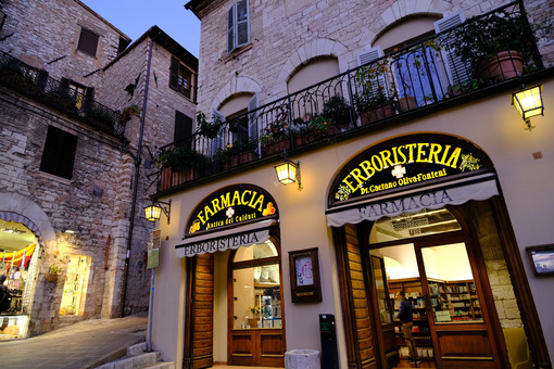 Municipality of Assisi square with old pharmacy and bar area. Illuminated signs in the city of San Francesco with the lights of the night. - LEphotoart.com