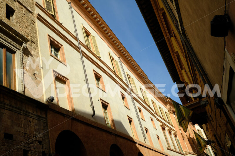 Narrow historic street in Foligno with flags on the facades of the houses. Glimpse in the historic center of the Umbrian town with wind. - MyVideoimage.com | Foto stock & Video footage