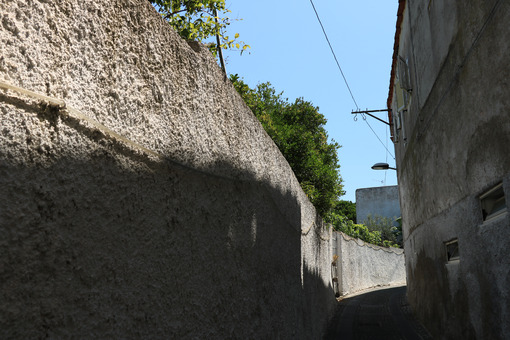 Narrow pedestrian street with white painted wall in southern Italy. Ischia island . Foto Ischia photos.